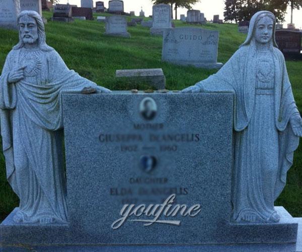 Religious cemetery headstone with grave decoration Jesus and Mary statue